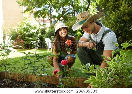 Young couple gardening outside, smiling happy. - stock photo
