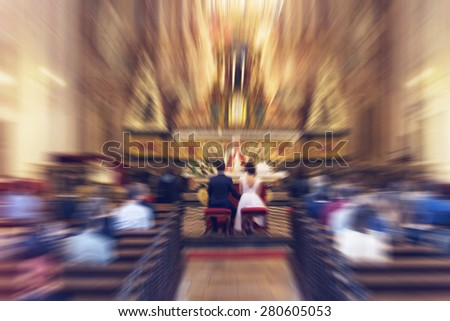 Young couple getting married in christian church - religious wedding - radial zoom blur applied, defocused, with instagram filter  - stock photo