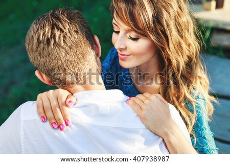Young couple.Girl has closed eyes and smiling, waist up, closeup. Man's back, rear view. Woman wearing blue dress and has pink manicure and man wearing white shirt - stock photo