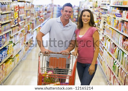 Young couple grocery shopping in supermarket - stock photo