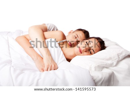 Young couple happily sleeping in white bed, isolated. - stock photo