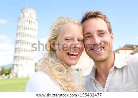 Young couple happy having fun on travel to Pisa. Tourists traveling visiting The Leaning Tower of Pisa. Beautiful laughing couple in love on romantic holidays vacation. Tower of Pisa, Tuscany, Italy. - stock photo