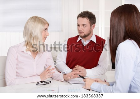 Young couple has consultation with consultant at desk at office. - stock photo