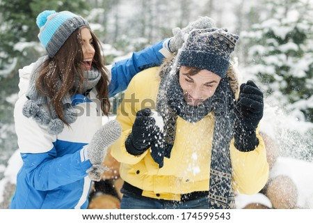 Young couple have fun during the snowball fight - stock photo