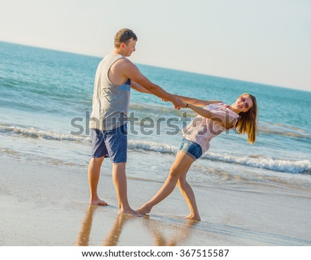 Young couple have fun  on the beach  at sunset - stock photo