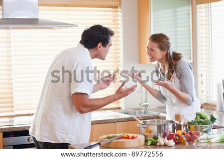 Young couple having a fight in the kitchen - stock photo