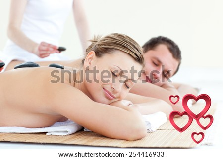 Young couple having a massage with hot stone against pink hearts - stock photo