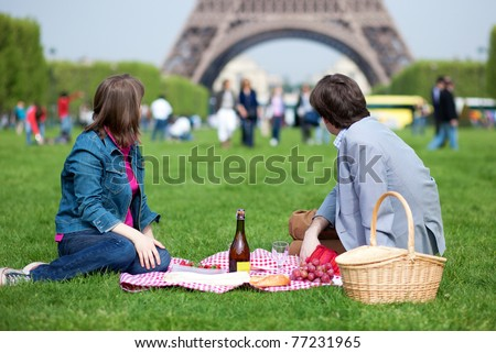 Young couple having a picnic near the Eiffel tower - stock photo