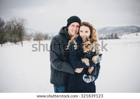 Young couple having a walk with their dog in snowy countryside - stock photo