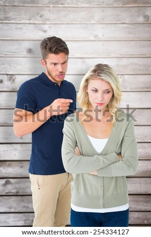 Young couple having an argument against wooden planks - stock photo