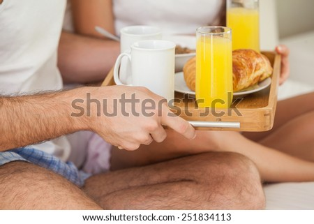 Young couple having breakfast in bed at home in bedroom - stock photo