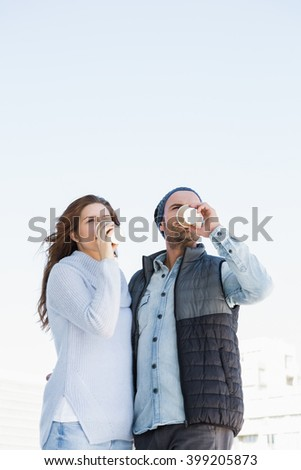 Young couple having coffee together outdoors - stock photo