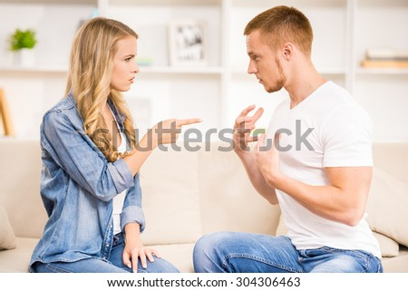 Young couple having disput on a sofa at home. - stock photo