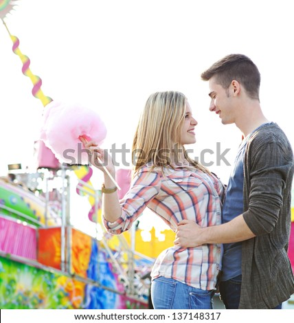 Young couple having fun in a colorful amusement park arcade, holding cotton candy and hugging and being romantic. - stock photo