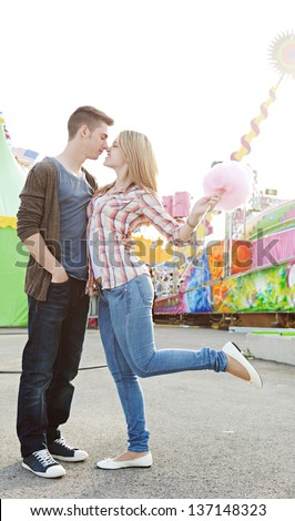 Young couple having fun in an attractions park arcade, holding cotton candy and rubbing their noses together. - stock photo