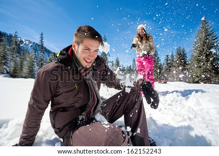 young couple having fun in snow,  outside - stock photo