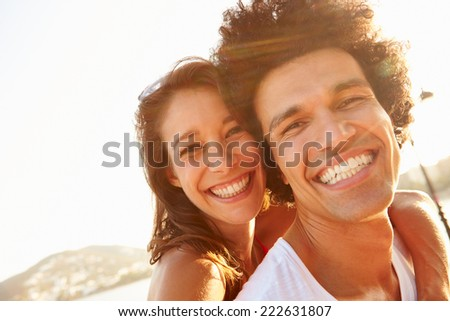 Young Couple Having Fun On Beach Holiday Together - stock photo