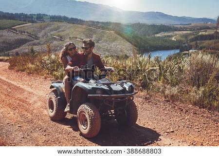 Young couple having fun on mountain while driving a quad bike on a summer day. Young man and woman on an ATV. - stock photo