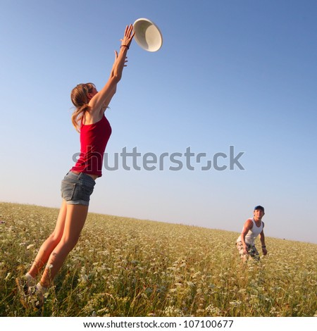 Young couple having fun with a disc on a summer meadow - stock photo