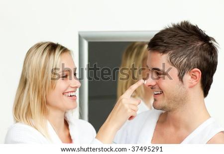 Young couple having fun with cream in bathroom - stock photo