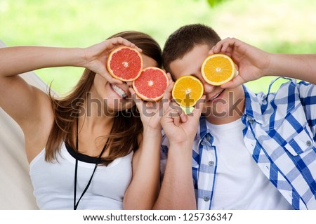 Young couple having fun with fruits - stock photo