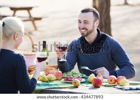 Young couple having picnic in sunny spring day at countryside and smiling - stock photo
