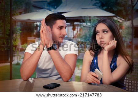 Young Couple Having Problems with Their Smart Phones - Young adult couple with smart phones upset out on a date   - stock photo