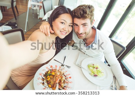 Young couple having romantic lunch in a fancy restaurant - stock photo