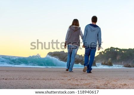 Young couple having romantic walk along sunset beach. - stock photo