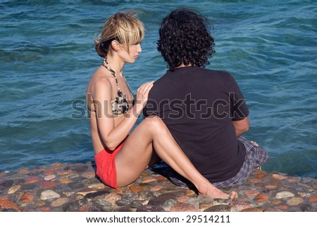 Young couple having serious conversation at the beach - stock photo