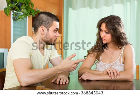 Young couple having serious conversation in home interior - stock photo