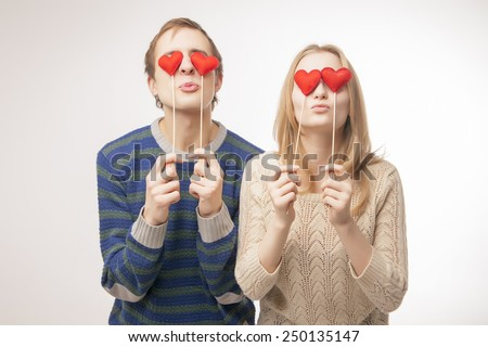 Young couple hiding their lips behind  little red hearts. Isolated over pink background. - stock photo