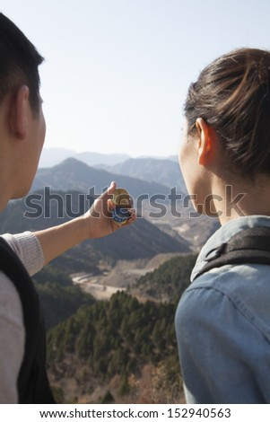 Young couple hiking and looking at the compass - stock photo