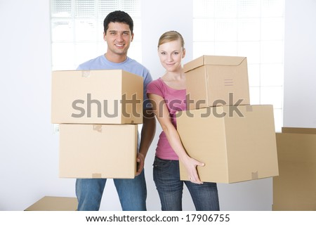 Young couple holding cardboard boxes. They're smiling and looking at camera. Front view. - stock photo