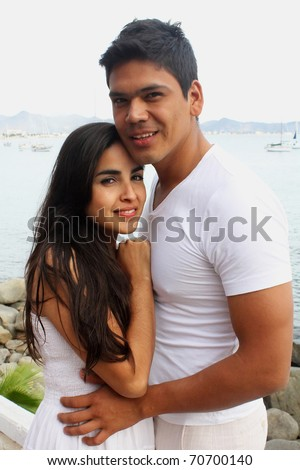 Young couple holding each other in front of the ocean - stock photo