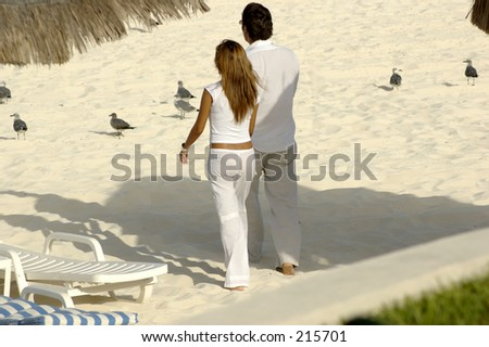Young couple holding hands and walking along the beach towards the ocean. - stock photo