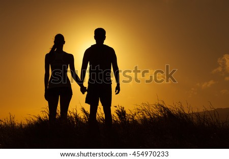 Young couple holding hands and watching the beautiful sunset.  - stock photo