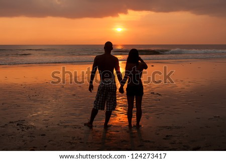 Young couple holding hands at sunset on beach - stock photo