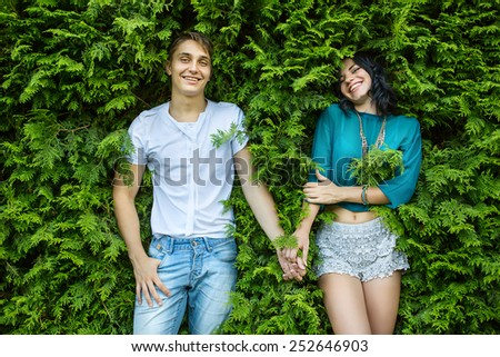 Young couple holding hands on the back is bright green foliage. Looking at the camera. Top view. - stock photo