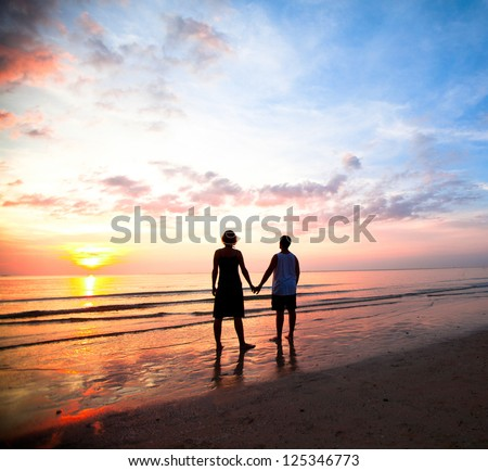 Young couple holding hands on the sea beach at sunset. - stock photo