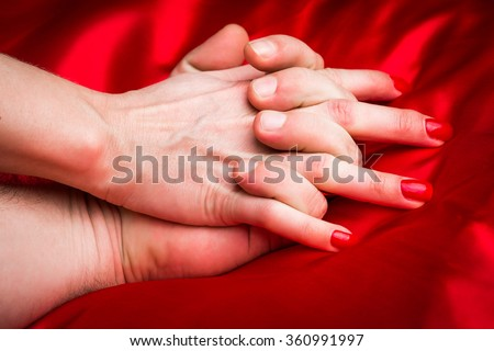 Young couple holding hands sensually on red silk bed. - stock photo