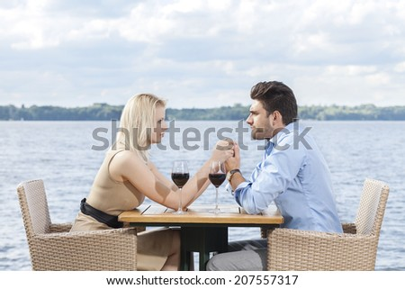 Young couple holding hands while looking at each other at outdoor restaurant by lake - stock photo