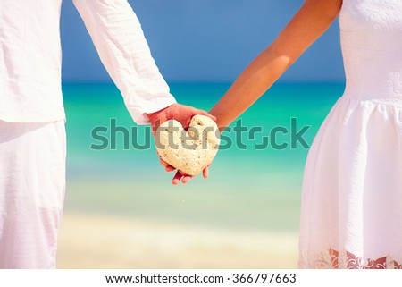 young couple holding heart shape stone on tropical beach - stock photo