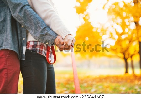 Young couple holding leash together in autumn park - stock photo