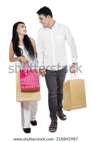 Young couple holding many shopping bags isolated on white - stock photo