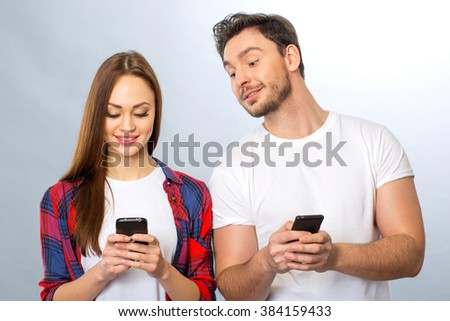 Young couple holding mobile phones - stock photo