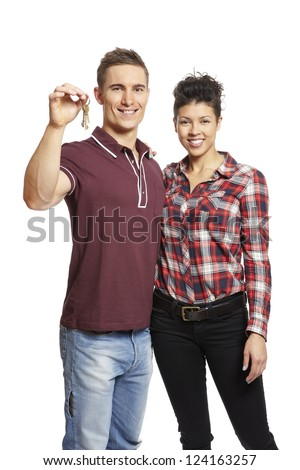 Young couple holding set of house keys on white background smiling - stock photo