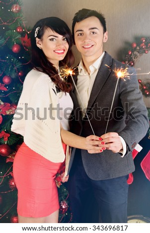 Young couple holding sparklers near a tree - stock photo