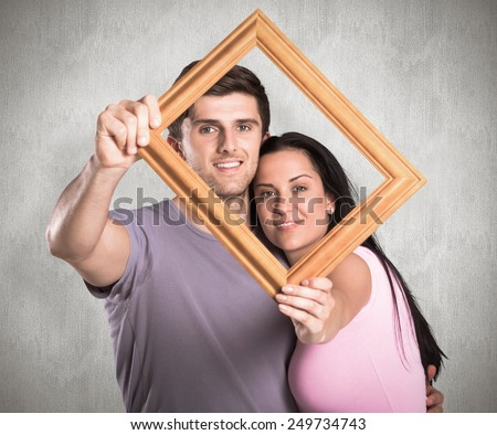 Young couple holding up frame against weathered surface - stock photo