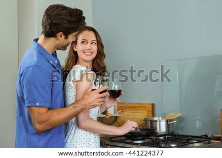 Young couple holding wine glass in kitchen at home - stock photo